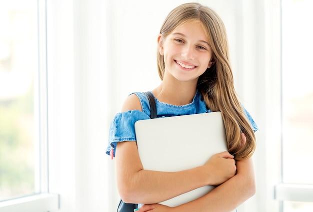 光にラップトップを保持しているバックパックを持つうれしそうな女の子 Premium写真