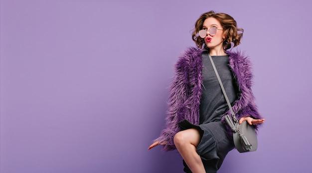 Радостная девушка с вьющимися каштановыми волосами танцует на фиолетовом фоне с выражением лица поцелуя
