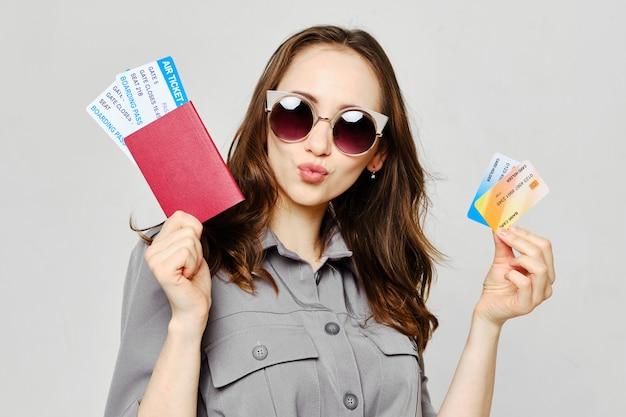 Радостная девушка в очках с авиабилетами и кредитными банковскими картами