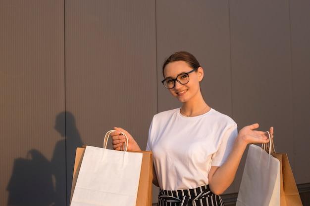 Радостная девушка с покупками возле торгового центра