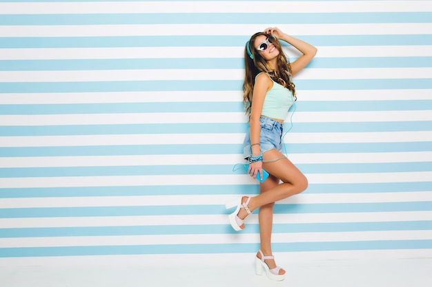 Joyful girl with tanned skin wearing tank-top and shorts dancing, listening favorite music. full-length portrait of pretty young woman in earphones with mobile phone having fun in home.