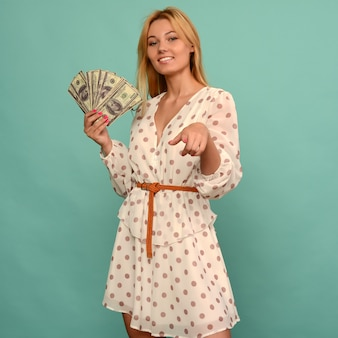 Joyful girl won the lottery and holds a fan of us dollars in her hands on a blue background