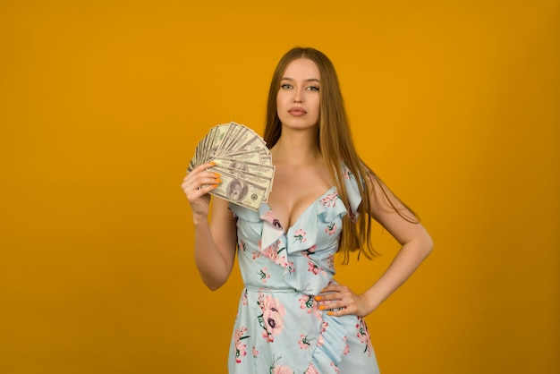 Joyful girl won the lottery and holds a fan of us dollars in her hands on a yellow background