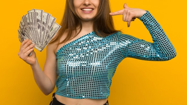 Joyful girl won the lottery and pointing on fan of us dollars in her hands on a yellow background - image