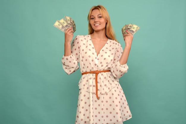 うれしそうな女の子が宝くじに当選し、青い背景に米ドルのファンを手に持っています