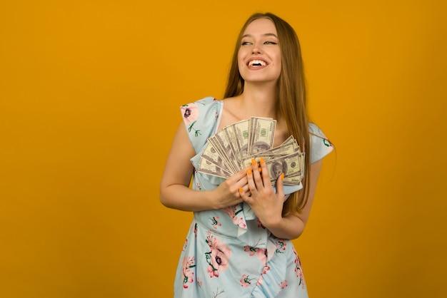 うれしそうな女の子が宝くじに当選し、黄色の背景に米ドルのファンを手に持っています