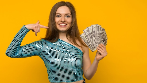 うれしそうな女の子が宝くじに当選し、黄色の背景に彼女の手で米ドルのファンを指しています-画像