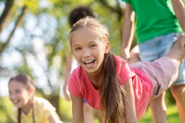 Радостные девочки и мальчики, активно играющие в парке