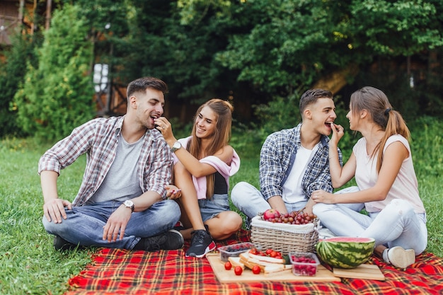 Joyful girls and boys spend weekend outdoor on picnic and eating fruits