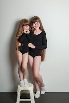 スポーツレオタードのうれしそうな女の子は、緑豊かなパンケーキと健康な髪の黒いヨガマットの上に立っています