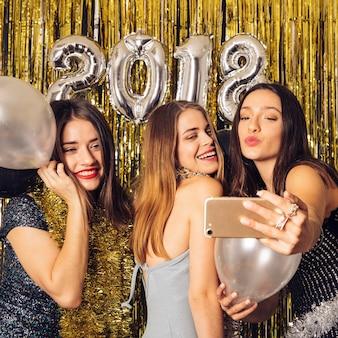 Ragazze gioiose che prendono selfie sul partito di nuovo anno
