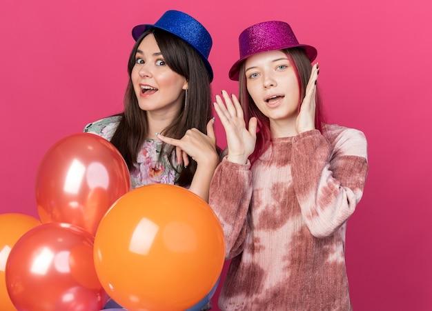 분홍색 벽에 격리된 전화 제스처를 보여주는 풍선을 들고 파티 모자를 쓴 즐거운 소녀들