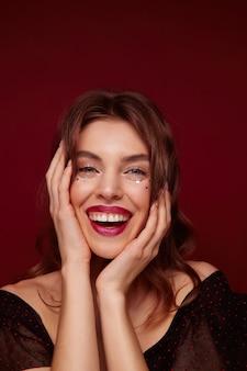 Gioiosa gloriosa giovane donna bruna con trucco festoso vestita di nero top con puntini rossi mentre si sta in piedi su sfondo bordeaux, tenendo il viso con le mani e sorridendo felicemente
