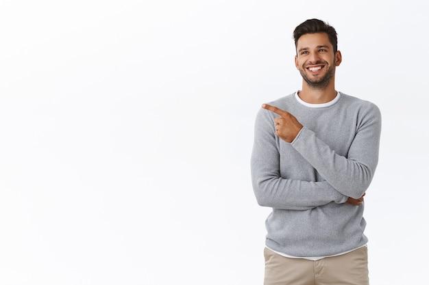 灰色のセーターを着た、うれしそうな格好良いフレンドリーなひげを生やした男、面白いジョークや広告から笑い、のんびりと喜んで笑い、友人とチャットし、左を指して、白い壁