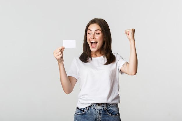 Gioiosa bella ragazza che si rallegra e guarda la carta di credito, pompa pugno mentre trionfa, bianco.