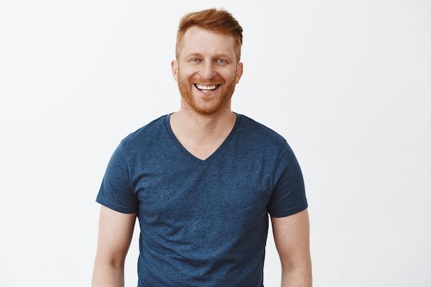 Радостный симпатичный обыкновенный мужчина с рыжими волосами и щетиной в синей футболке, широко улыбаясь