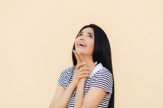 Радостная великолепная молодая женская модель радостно смотрит вверх и держит руку под подбородком