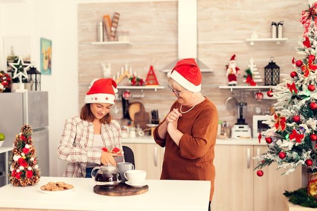 Радостная бабушка в красной шляпе дарит племяннице рождественскую подарочную коробку