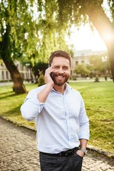 즐거운 남자 30 대, 화창한 날에 도시 공원에서 걷고 휴대 전화로 말하기