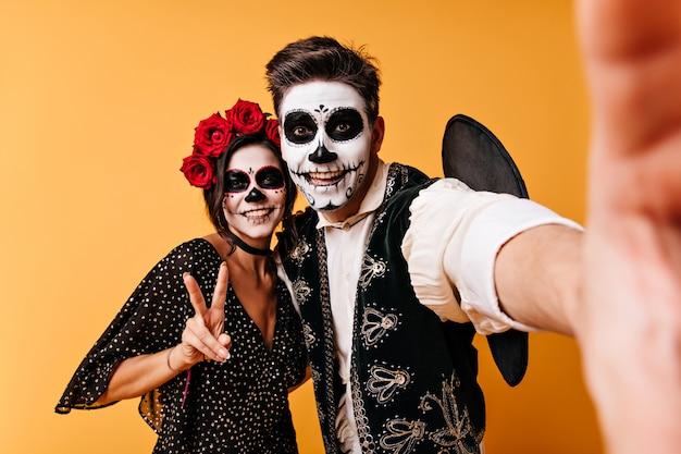 즐거운 남자와 여자는 할로윈 파티를 즐기고 있습니다. 커플 평화 기호를 보여주는 특이 한 옷에 selfie를 걸립니다.