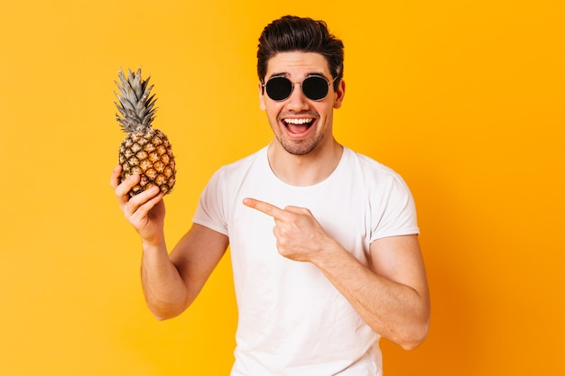 Joyful guy dressed in white t-shirt and glasses points to pineapple and smiles on orange space.