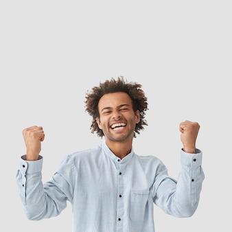 うれしそうな男のジェスチャー、勝利で拳を食いしばり、目を閉じて笑顔を保ち、のんびりと感じ、何かを祝い、エレガントなシャツを着て、白い壁に隔離