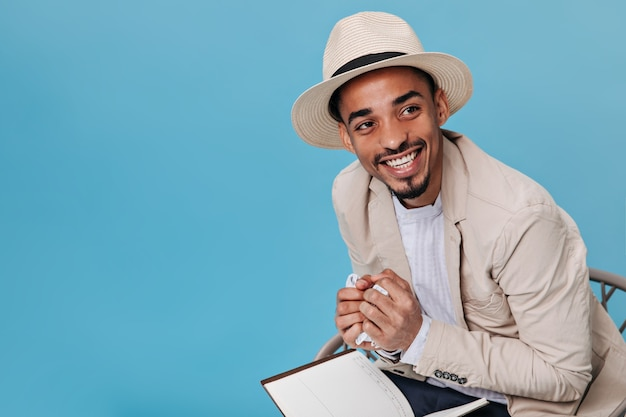 Joyful guy in hat and beige jacket smiling and posing on blue wall