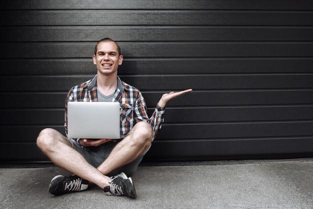 足を組んで床に座っているラップトップと格子縞のシャツを着たうれしそうな男