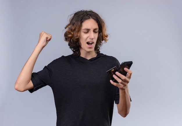 白い壁に電話とカードを保持している黒いtシャツの長い髪のうれしそうな男