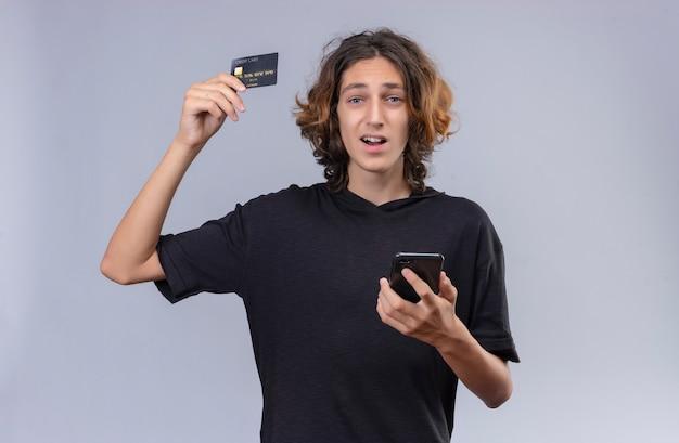 흰 벽에 전화와 은행 카드를 들고 검은 티셔츠에 긴 머리를 가진 즐거운 남자