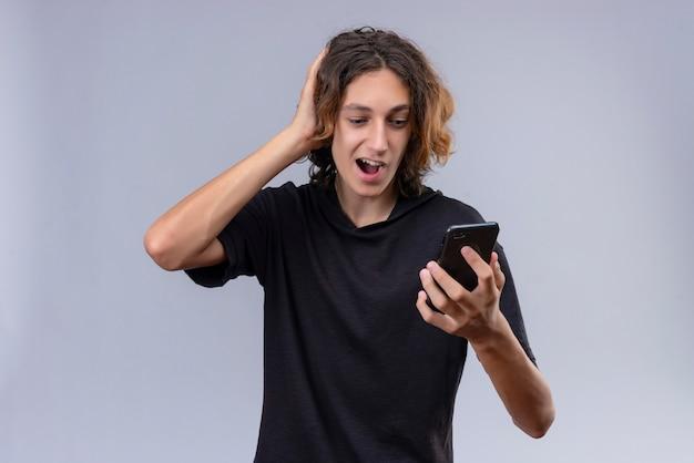 전화를 들고 흰 벽에 그의 머리를 잡은 검은 티셔츠에 긴 머리를 가진 즐거운 남자