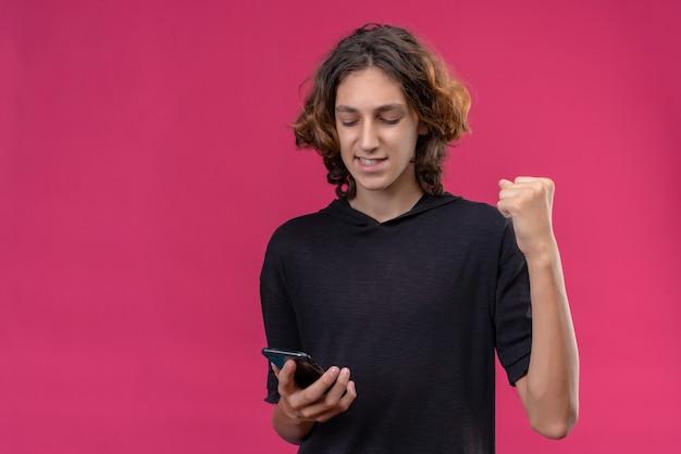 분홍색 벽에 전화를 들고 검은 티셔츠에 긴 머리를 가진 즐거운 남자