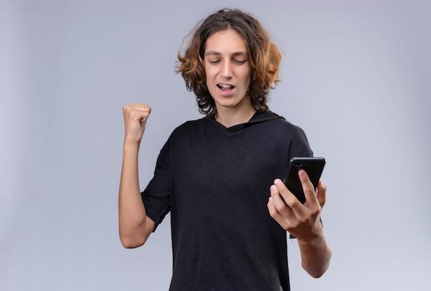흰 벽에 전화를 들고 검은 티셔츠에 긴 머리를 가진 즐거운 남자