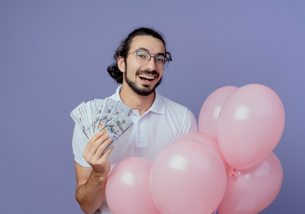 Joyful hadnsome man wearing glasses holding cash and balloons isolated on purple background