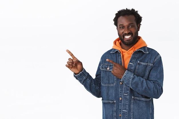 Радостный красивый афро-американский мужчина дает направление или совет, в осенней теплой джинсовой куртке, оранжевой толстовке с капюшоном, указывая в левый верхний угол