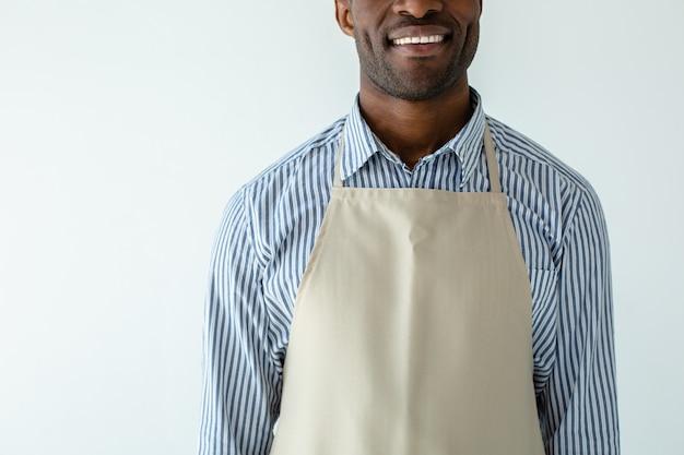 Радостный красивый афроамериканский официант ждет гостей, улыбаясь