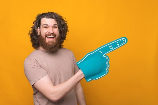 Радостный красивый бородатый мужчина улыбается и показывает перчаткой вентилятора