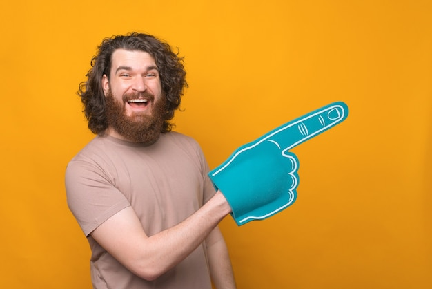 Joyful handsome bearded man smiling and pointing with fan glove