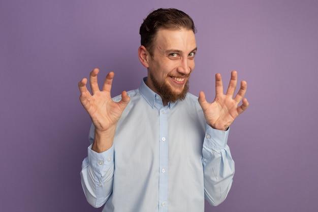 Uomo biondo bello allegro che gesturing le zampe della tigre isolate sulla parete viola
