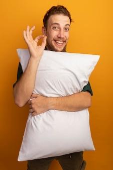 うれしそうなハンサムなブロンドの男は枕とジェスチャーを保持しますオレンジ色の手サイン