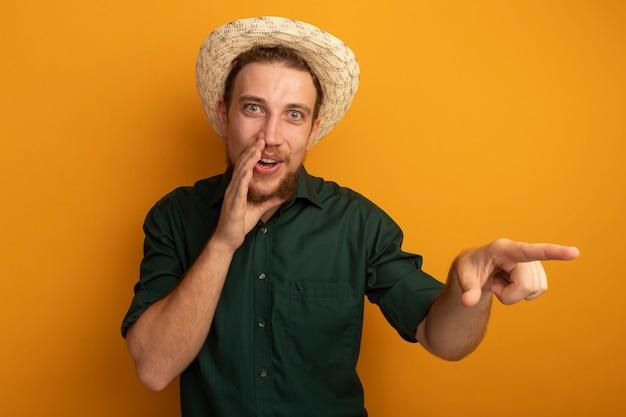 Gioioso bell'uomo biondo con cappello da spiaggia tiene la mano vicino alla bocca e indica il lato isolato sulla parete arancione