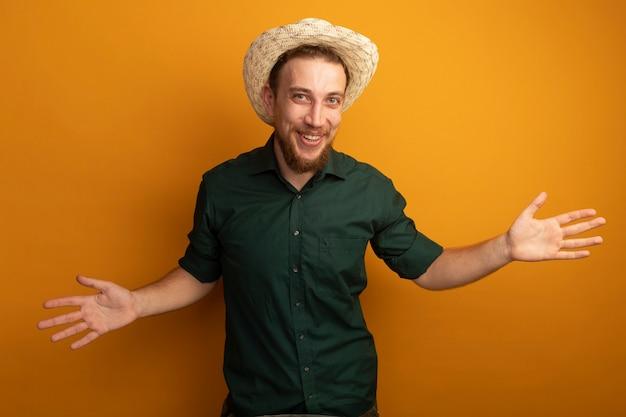 ビーチ帽子を持つうれしそうなハンサムなブロンドの男は、オレンジ色の壁で隔離の手を開いた