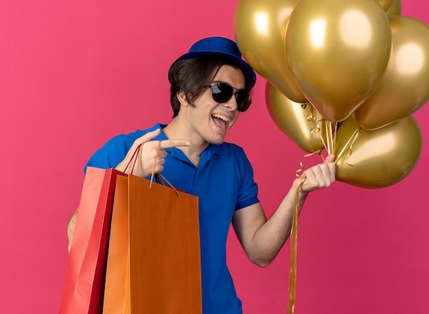 파란색 파티 모자를 쓰고 태양 안경에 즐거운 잘 생긴 백인 남자는 헬륨 풍선과 측면을 가리키는 종이 쇼핑백을 보유하고 있습니다.