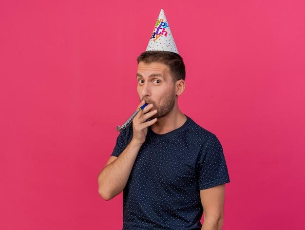 コピースペースでピンクの背景に分離された誕生日の帽子を吹くパーティーの笛を身に着けているうれしそうなハンサムな白人男性