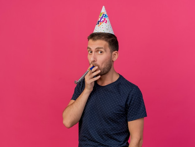 Joyful handsome caucasian man wearing birthday cap blowing party whistle isolated on pink background with copy space