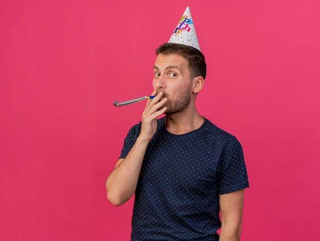 Gioioso bell'uomo caucasico indossando il cappello di compleanno che tiene e che soffia fischio di partito isolato su sfondo rosa con copia spazio