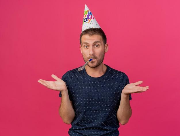 誕生日の帽子をかぶってうれしそうなハンサムな白人男性は、コピースペースでピンクの背景に分離された笛を吹いて手を開いて保持します。