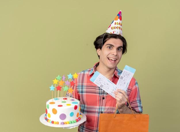 Joyful handsome caucasian man wearing birthday cap holds paper shopping bag air tickets and birthday cake