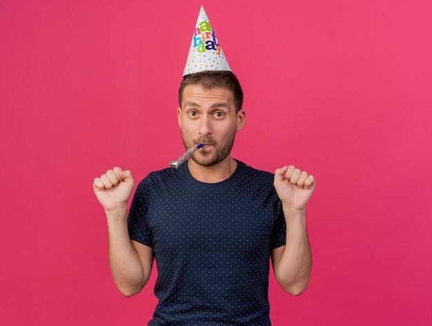 誕生日のキャップを身に着けているうれしそうなハンサムな白人男性は、コピースペースでピンクの背景に分離された拳吹くパーティー笛を維持します