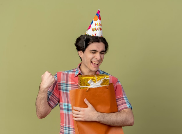 Joyful handsome caucasian man wearing birthday cap keeps fist and holds gift box in paper shopping bag